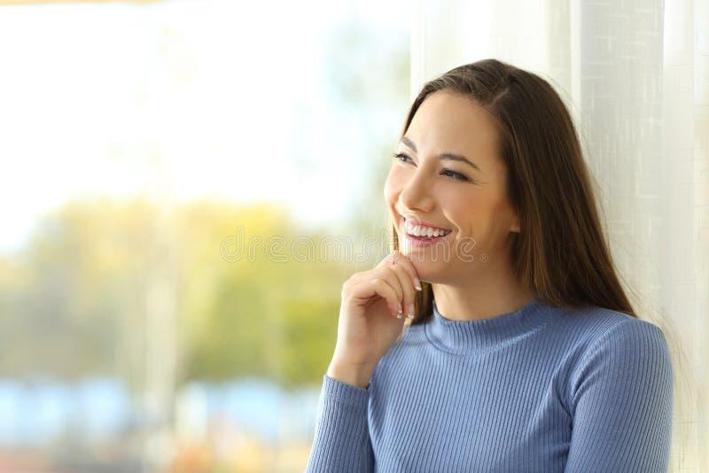 Smileykvinna som tänker och ser sidan royaltyfria bilder