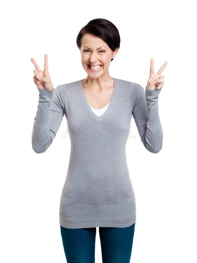 Smileykvinnan visar segertecknet med två händer fotografering för bildbyråer