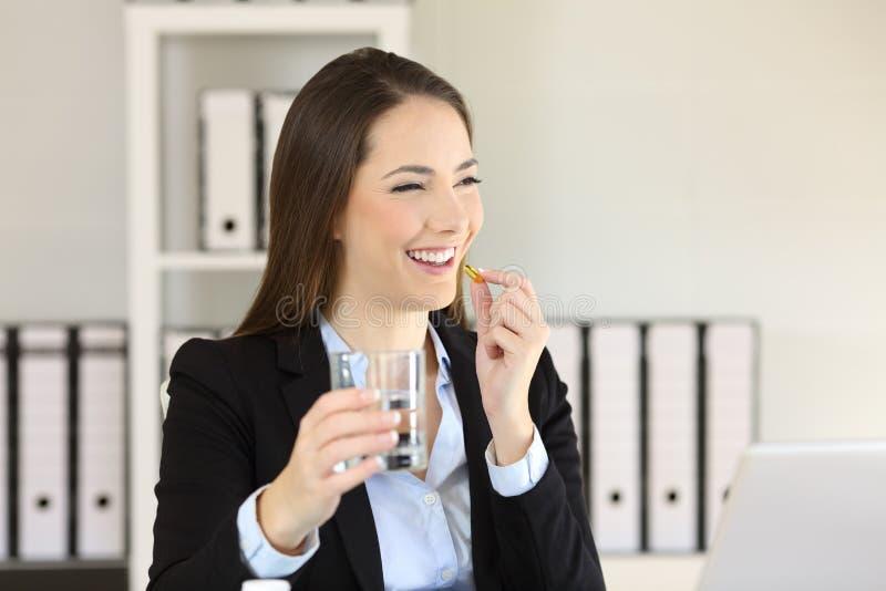 Smileyonderneemster die een pil nemen op kantoor stock fotografie