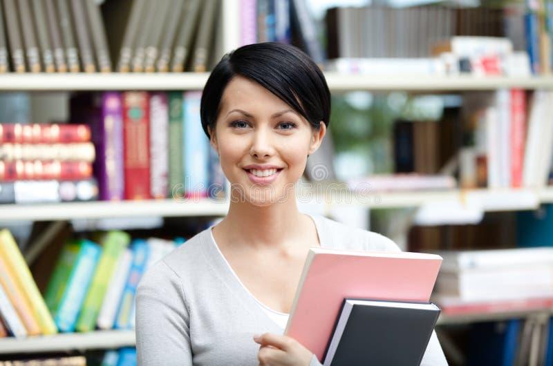 Smileystudent met boek bij de bibliotheek royalty-vrije stock afbeelding