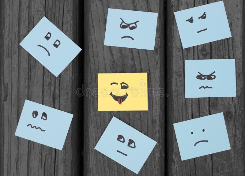 Smilies infelices y una cara feliz pintada en etiquetas engomadas de la oficina fotografía de archivo libre de regalías
