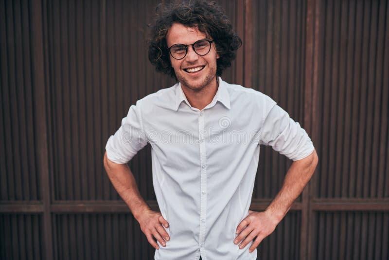 smilimg英俊的年轻商人室外射击戴摆在的眼镜的户外 摆在对棕色墙壁的男生 聪明的人 免版税库存图片