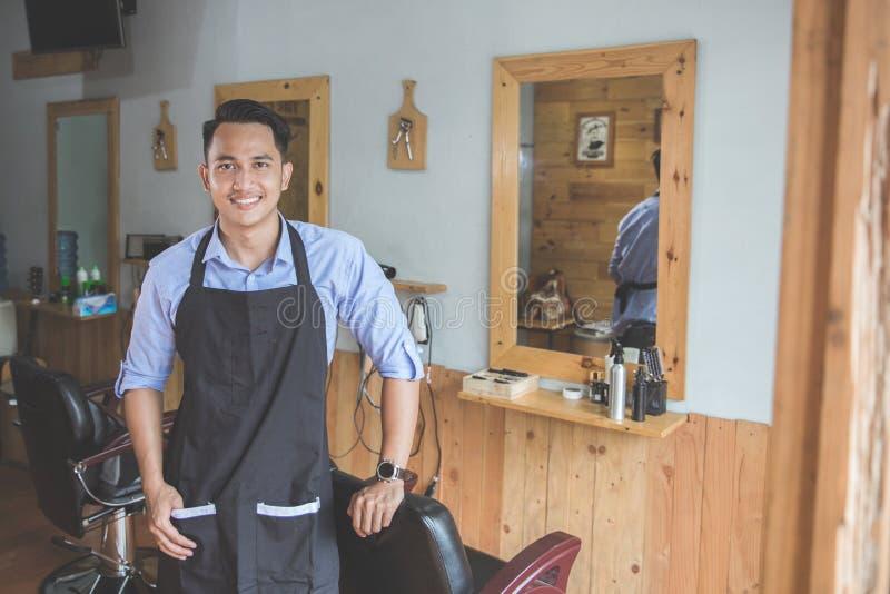 Smilin experto del peluquero joven que mira la cámara en barbería fotografía de archivo libre de regalías