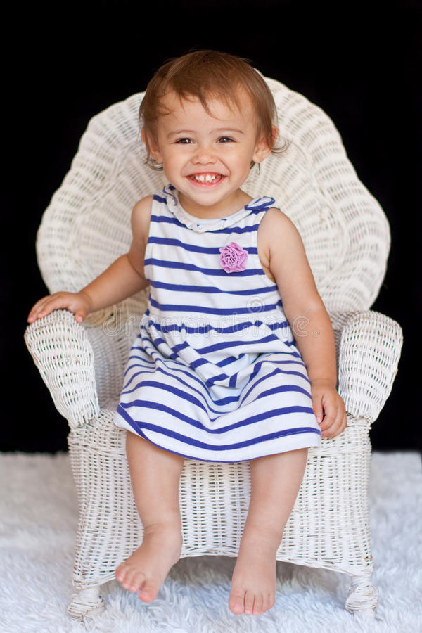 Smiling 1 year old multicultural girl in chair. A happy, smiling one-year old multicultural, asian and caucasian, girl has direct eye contact with the royalty free stock photos