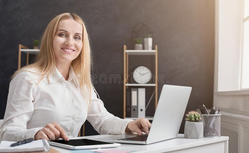 Smiling accountant sitting by laptop and looking at camera royalty free stock photography