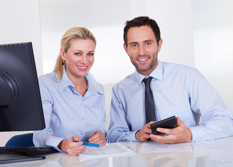 Smiling accountants discussing reports stock images