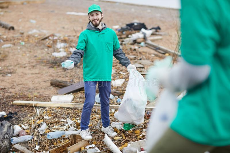 Smiling activist with rubbish bag. Cheerful young volunteer in green uniform standing with garbage bag while cleaning place from garbage stock image