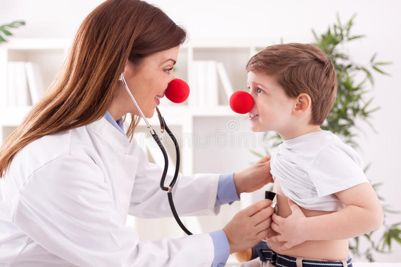 Smiling adorable female doctor clown listen patient heart royalty free stock photos