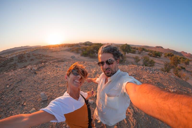 Smiling adult couple taking selfie in the Namib desert, Namib Naukluft National Park, main travel destination in Namibia, Africa. Fisheye view in backlight stock photo