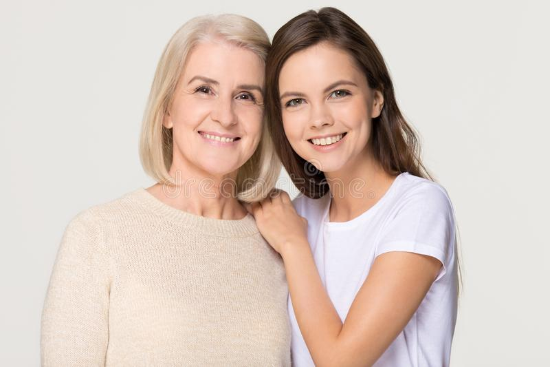 Smiling adult daughter and old mother bonding isolated on background royalty free stock photos