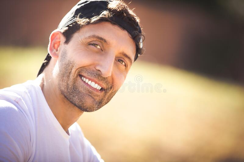 Smiling adult man with hat on his head outdoors. Curly hair royalty free stock photos