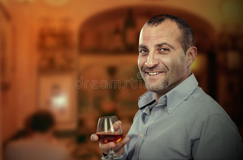 Download Smiling Adult Man Posing With Glass Of Brandy Stock Photo - Image: 90046750