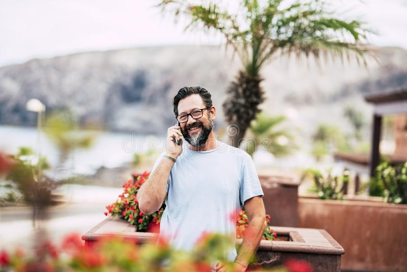 Smiling adult man talking at the phone outdoor at home -  people and technology in leisure. activity with defocused background. Cheerful standing caucasian royalty free stock photos