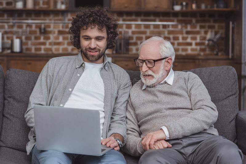 Smiling adult son and senior father using laptop. At home royalty free stock images