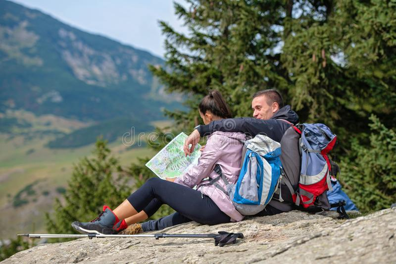 Smiling adventure couple with map on slope. look at map royalty free stock photo