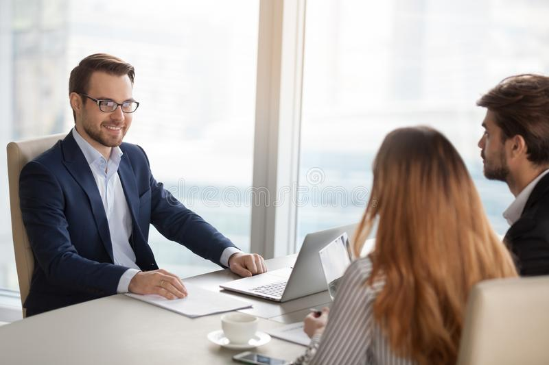 Smiling adviser manager or negotiator consulting business people at meeting royalty free stock images