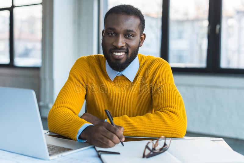 Smiling african american businessman holding pen and looking at camera. In office stock photos