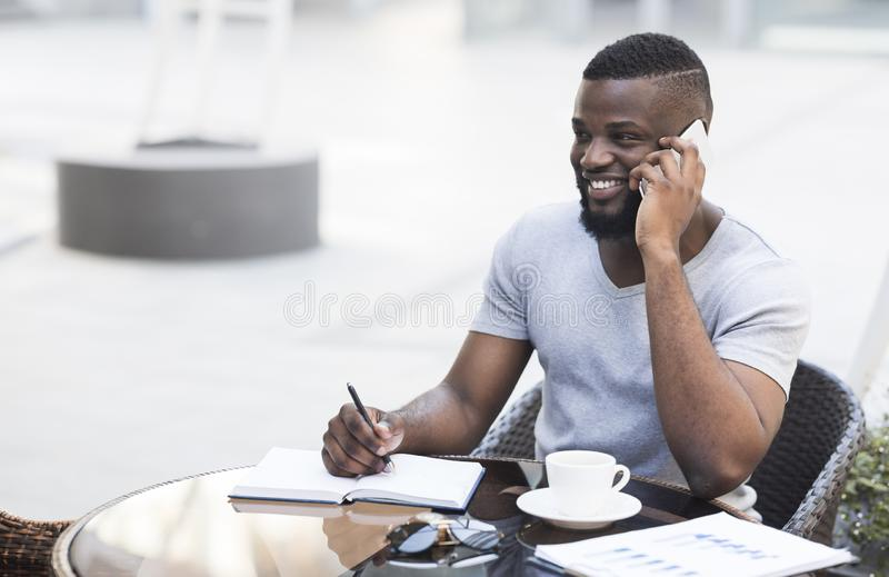 Smiling african american businessman with notepad in cafe royalty free stock image
