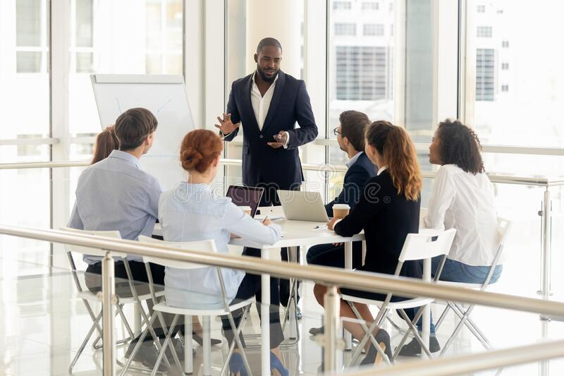 African American male coach make flip chart presentation for employees royalty free stock images