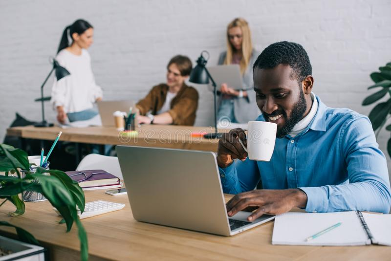 smiling african american businessman using laptop and drinking coffee from mug and coworkers working behind in modern royalty free stock photos