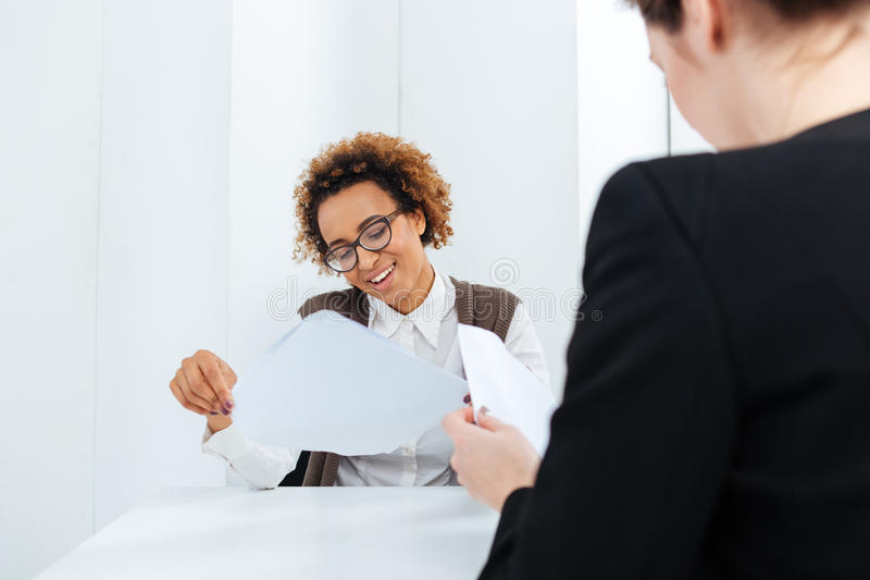 Smiling african american businesswoman having job interview and filling application royalty free stock photos