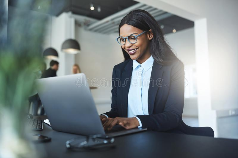 Smiling African American businesswoman using a laptop at her des stock image