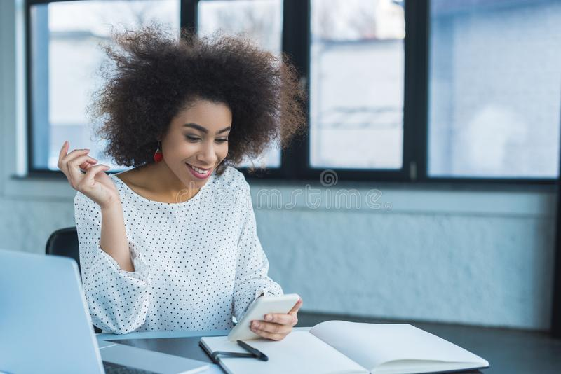 smiling african american businesswoman using smartphone royalty free stock photo
