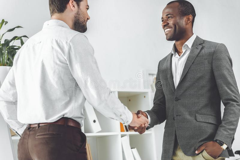 Smiling african american and caucasian businessmen. Shaking hands royalty free illustration
