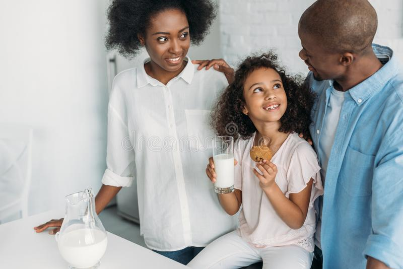 smiling african american child with glass of milk cookie in hands and parents near by in kitchen royalty free stock photos