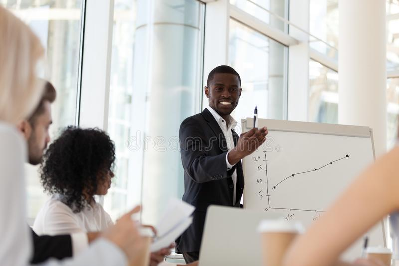 Smiling African American coach give flipchart presentation to em royalty free stock photo