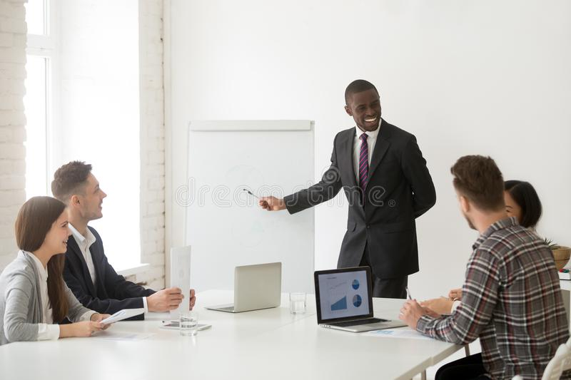 Smiling african-american coach in suit discussing business prese stock photos
