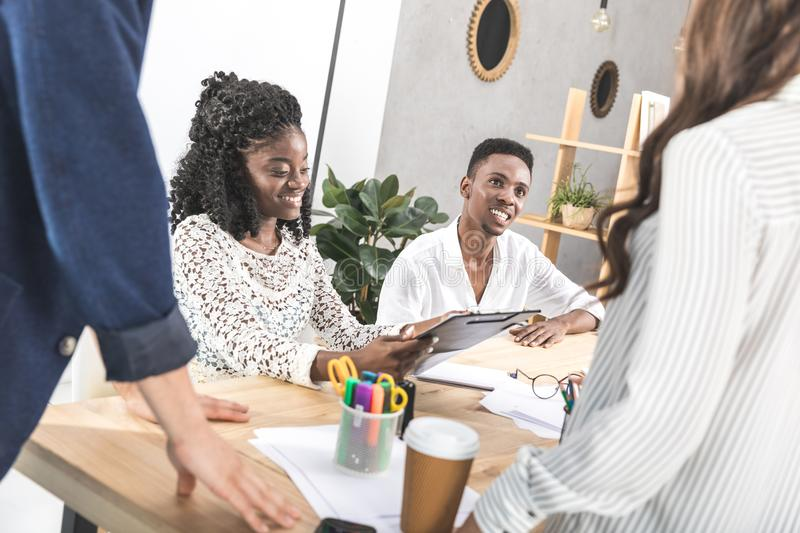 smiling african american colleagues at business meeting at workplace stock images