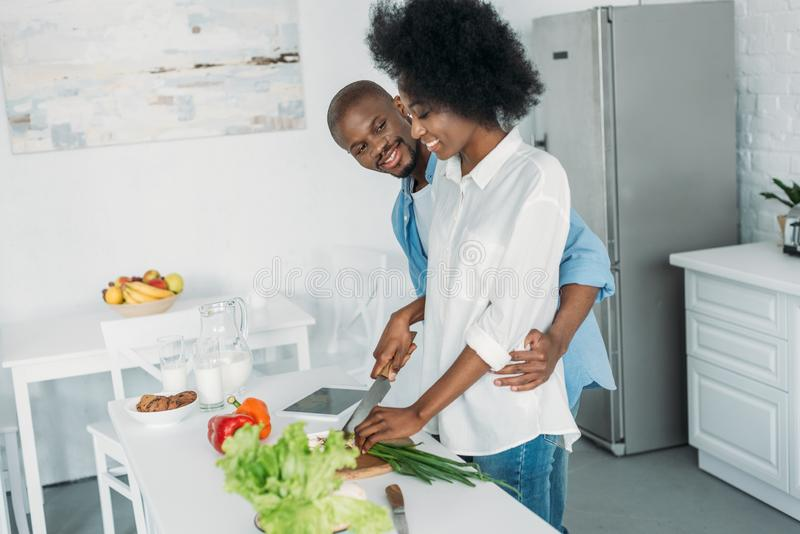 Smiling african american cooking breakfast together in kitchen. At home stock photography