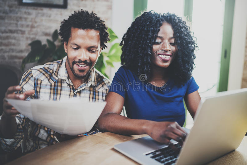 Smiling African american couple checking paper bills together at the wooden table.Young black man and his girlfriend stock photos