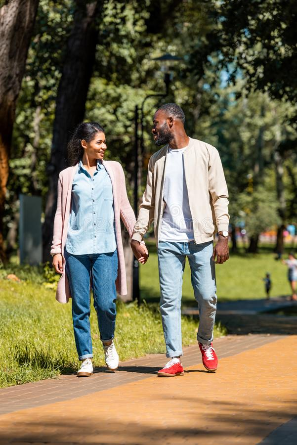 smiling african american couple holding hands and walking royalty free stock image