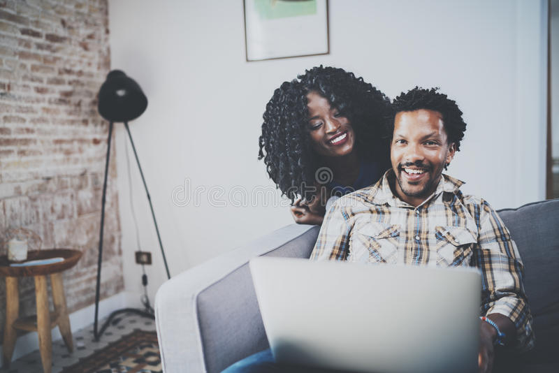 Smiling african american couple relaxing together on the couch.Young black man and his girlfriend using laptop at home stock images