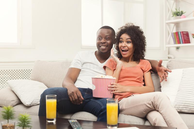 Happy african-american couple watching TV at home stock photo