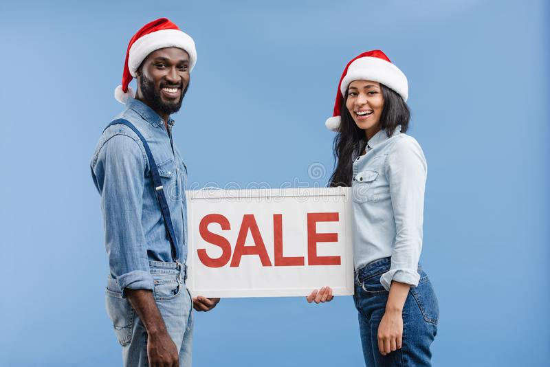 smiling african american couple in santa hats holding sale sign royalty free stock photo