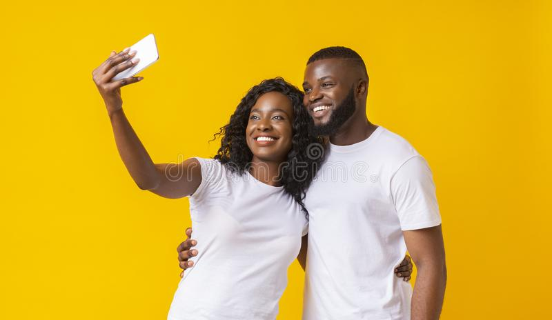 Lovely black guy and girl taking selfie on smartphone. Smiling African American Couple Taking Selfie on Smartphone, yellow studio background, copy space royalty free stock images