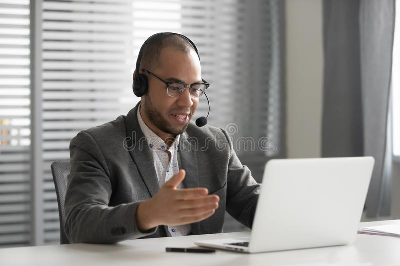 Smiling African American employee in headset using laptop, talking online stock images