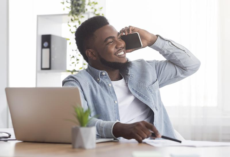 Smiling african american employee talking on mobile phone at workplace stock images