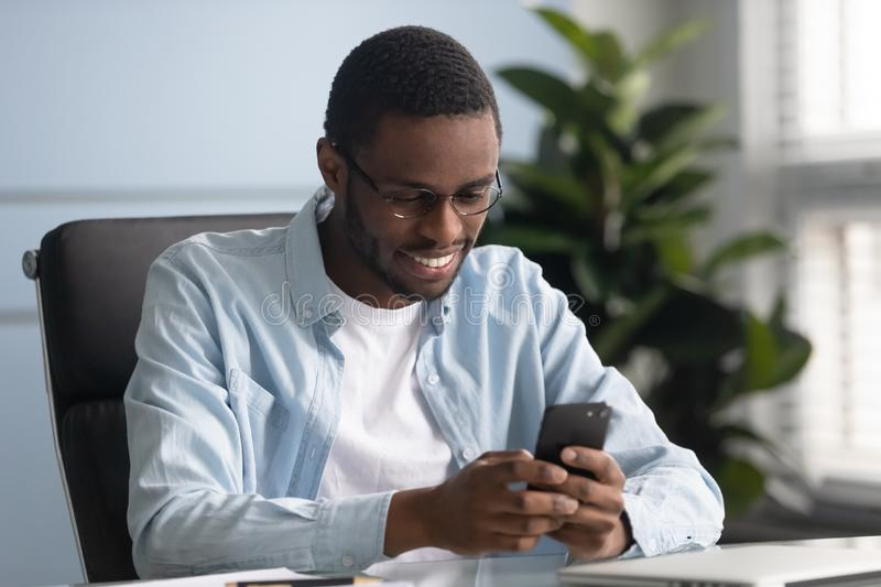 Smiling african american employee using mobile applications. royalty free stock photography