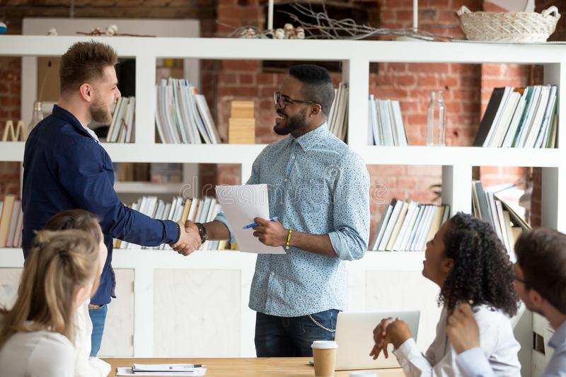 Smiling black CEO handshake Caucasian employee greeting with ach. Smiling African American employer handshake millennial worker greeting with good work result royalty free stock images