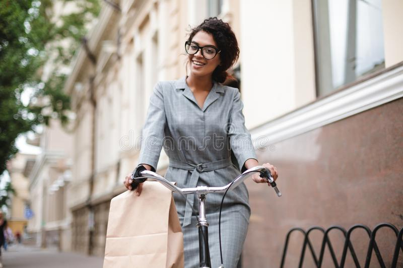 Smiling African American girl in glasses riding on bicycle and happily looking in camera. Young beautiful lady with dark. Portrait of smiling African American royalty free stock images