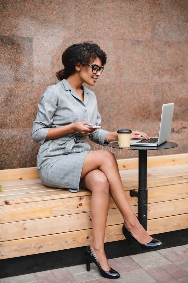 Smiling African American girl in glasses sitting on bench and working on her laptop with cellphone in hand. Lady with. Smiling African American girl in glasses royalty free stock photo