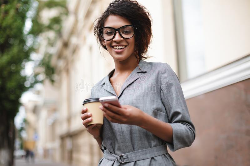 Smiling African American girl in glasses standing on street with cellphone and coffee in hands while happily looking in. Camera. Portrait of lady with dark royalty free stock photo