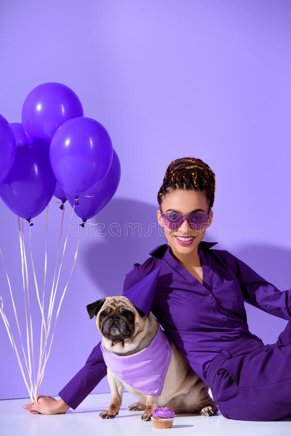 smiling african american girl posing with purple balloons and pug, ultra violet stock photo
