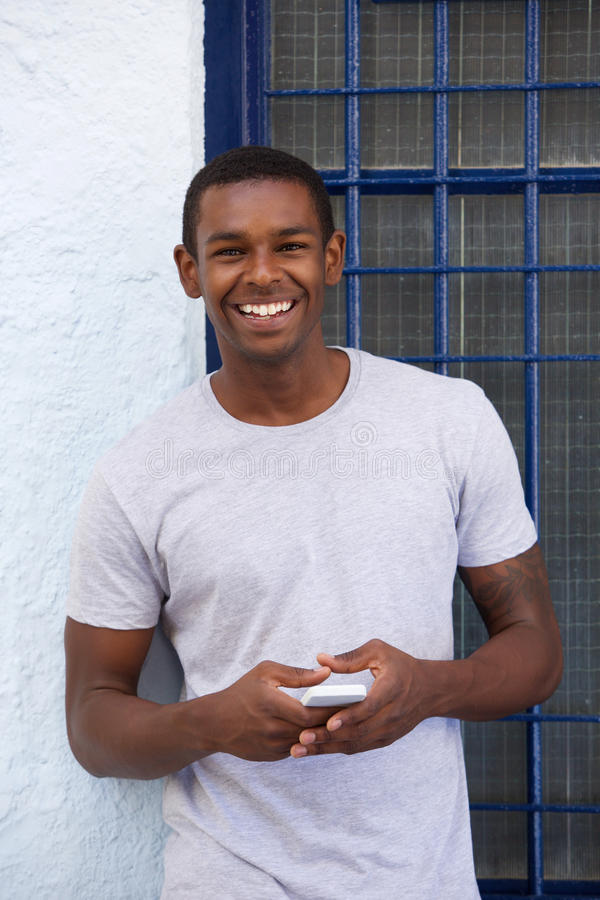 Smiling african american guy with cellphone stock photography