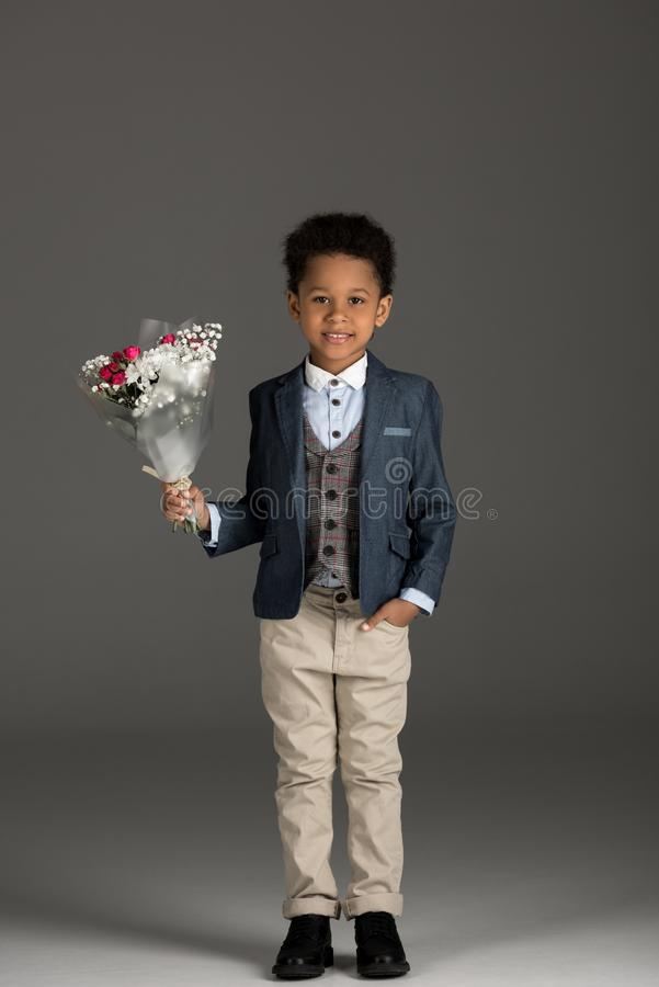 smiling african american kid standing with bouquet of flowers royalty free stock photo