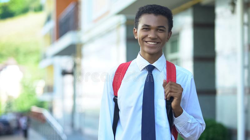 Smiling african-american male student with backpack posing on camera, education royalty free stock image